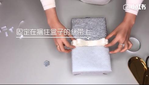 蝴蝶结固定在捆盒子的丝带上