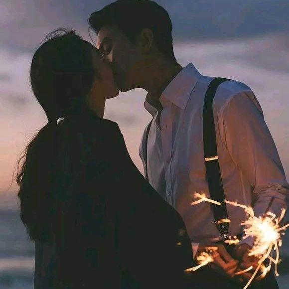 情侣手中拿着烟花在接吻